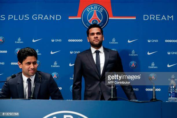 Paris Saint Germain's new Brazilian defender Dani Alves and PSG's Qatari president Nasser AlKhelaifi give a press conference on July 12 in Paris...