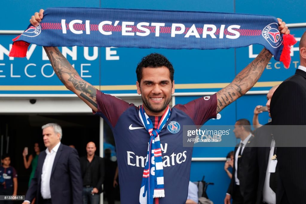 TOPSHOT - Paris Saint Germain's (PSG) new Brazilian defender Dani Alves poses with a scarf after a press conference on July 12, 2017, in Paris. Alves has signed a two-year deal with Paris Saint-Germain, the French club confirmed on July 12. / AFP PHOTO / Thomas SAMSON