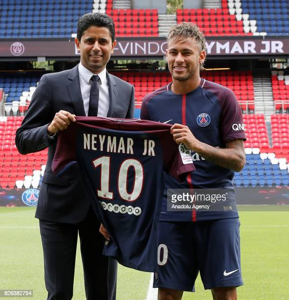 Paris Saint Germain's new Brazilian striker Neymar poses during his official presentation with PSG chairman and CEO Nasser AlKhelaif at the Parc des...