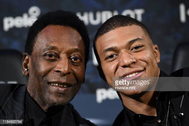 TOPSHOT Paris SaintGermain and France national football team forward Kylian Mbappe and Brazilian football legend Pele pose as they take part in a...
