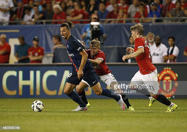 Paris SaintGermain forward Zlatan Ibrahimovic controls the ball against Manchester United defender Luke Shaw and defender Bastian Schweinsteiger...