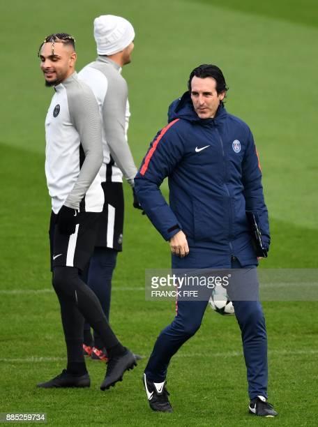 Paris SaintGermain French defender Layvin Kurzawa looks on as Paris SaintGermain's Spanish coach Unai Emery conducts a training session in...