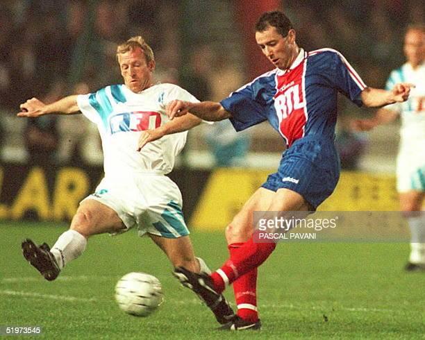Paris SaintGermain midfielder Alain Roche kicks the ball past Marseille's de Wolf during their French Cup semifinal 11 April in Paris Paris...