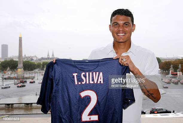 Paris Saint-Germain newly recruited Brazilian defender Thiago Silva poses with his new jersey in front of the place de la Concorde after a press...