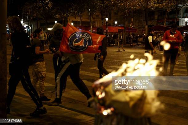 Paris Saint-Germain supporters wave a PSG flag as they walk past a burning trash bin on the Champs-Elysees in Paris on August 23 after the end of the...