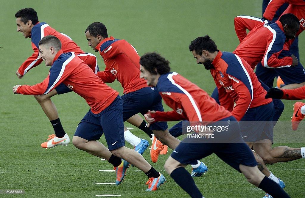 Paris Saint-Germain team players run during a training ...