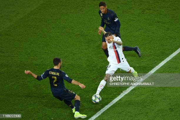 Paris SaintGermain's Argentine forward Mauro Icardi fights for the ball with Real Madrid's French defender Raphael Varane and Real Madrid's Spanish...