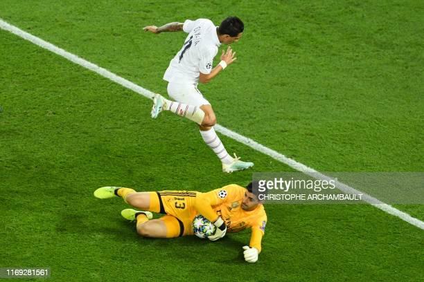 Paris Saint-Germain's Argentine midfielder Angel Di Maria jumps over Real Madrid's Belgian goalkeeper Thibaut Courtois during the UEFA Champions...