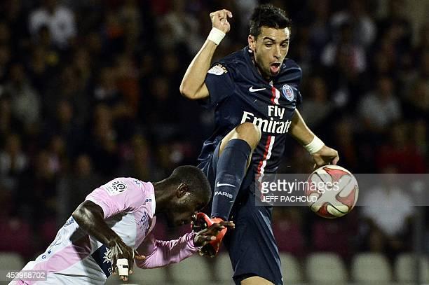 Paris SaintGermain's Argentine midfielder Javier Pastore challenges Evian TG's Ghanaian defender Jonathan Mensah during the French L1 football match...