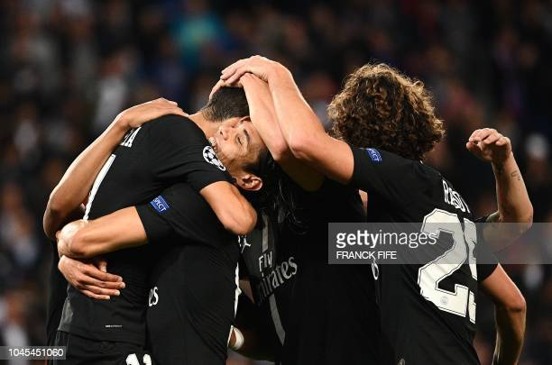 TOPSHOT Paris SaintGermain's Argentinian forward Angel Di Maria is congratulated by teammates after scoring a goal during the UEFA Champions' League...