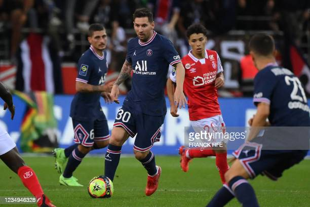 Paris Saint-Germain's Argentinian forward Lionel Messi runs with the ball during the French L1 football match between Stade de Reims and Paris...