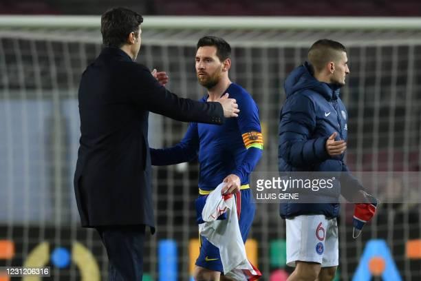 Paris Saint-Germain's Argentinian head coach Mauricio Pochettino speaks to Barcelona's Argentinian forward Lionel Messi next to Paris Saint-Germain's...