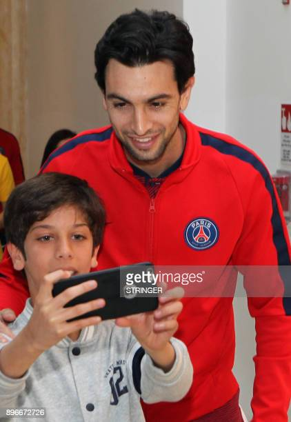 Paris SaintGermain's Argentinian midfielder Javier Pastore poses with a fan at a shopping mall in Doha as part of their winter tour in the Qatari...