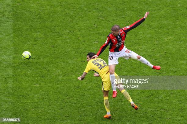 Paris SaintGermain's Brazilian defender Dani Alves and Nice's French defender Maxime Le Marchand go for a header during the French L1 football match...