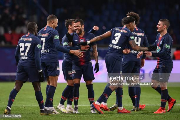 Paris SaintGermain's Brazilian defender Dani Alves celebrates with teammates after scoring their third goal during the French Cup semifinal football...