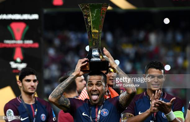 Paris SaintGermain's Brazilian defender Dani Alves holds the trophy as he celebrates with teammates after winning the French Trophy of Champions...