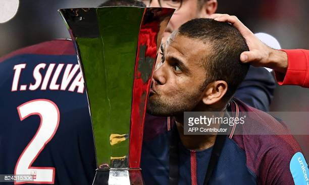 TOPSHOT Paris SaintGermain's Brazilian defender Dani Alves kisses the trophy as he celebrates with teammates after winning the French Trophy of...