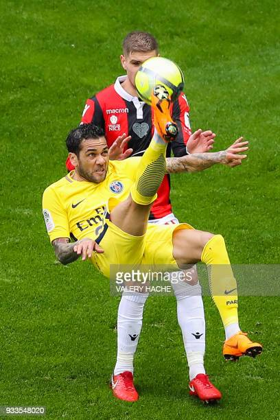 Paris SaintGermain's Brazilian defender Dani Alves performs a bicycle kicke despite Nice's French defender Maxime Le Marchand during the French L1...