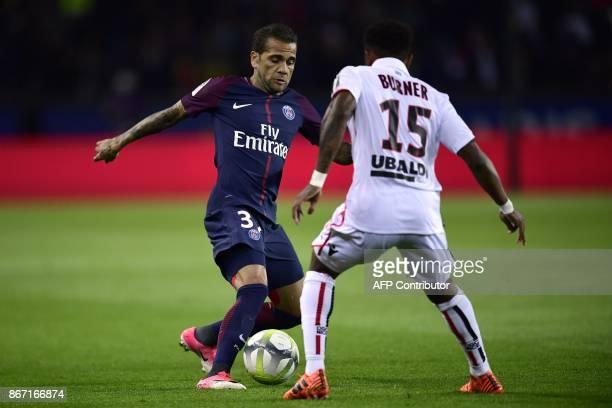 Paris SaintGermain's Brazilian defender Dani Alves vies with Nice's French defender Patrick Burner during the French L1 football match between Paris...
