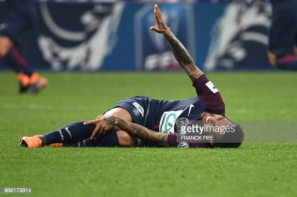 Paris SaintGermain's Brazilian defender Daniel Alves gestures as he lies on the ground during the French Cup final football match between Les...