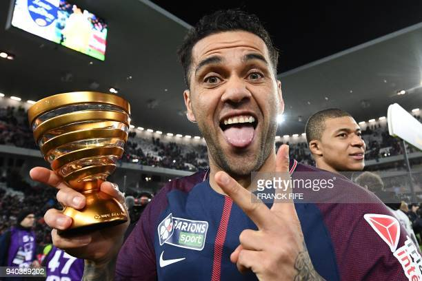 Paris SaintGermain's Brazilian defender Daniel Alves holds the trophy as he celebrates after victory in the French League Cup final football match...