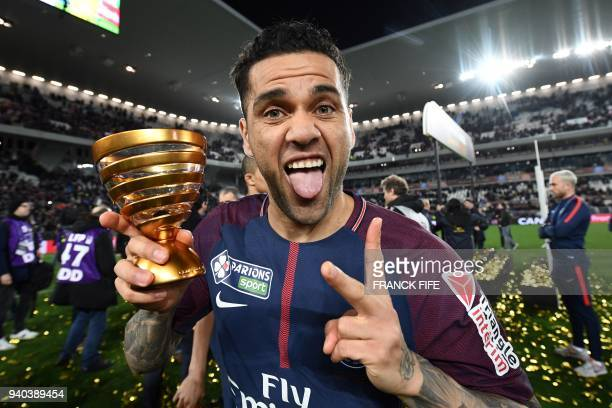 TOPSHOT Paris SaintGermain's Brazilian defender Daniel Alves holds the trophy as he celebrates after victory in the French League Cup final football...