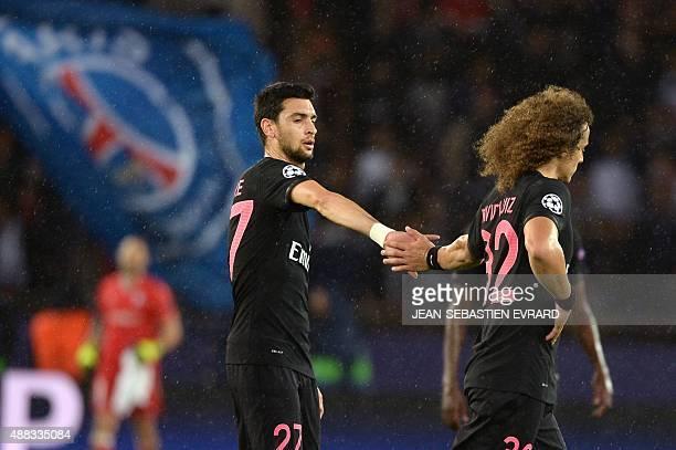 Paris SaintGermain's Brazilian defender David Luiz gets a high five from teammate Argentinian midfielder Javier Pastore at the end of the UEFA...