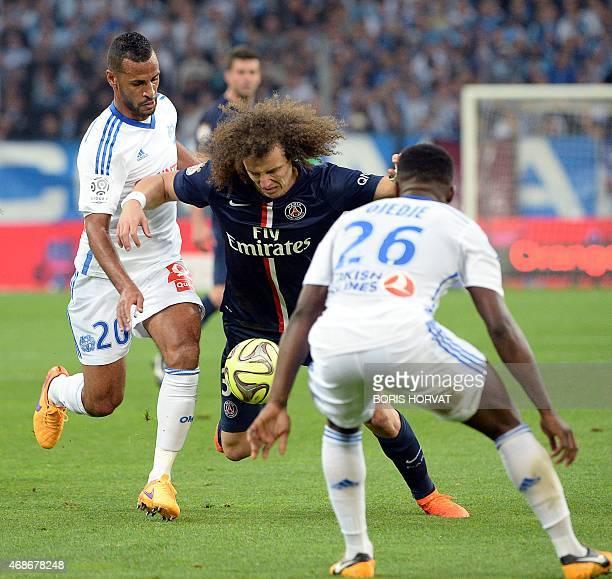 Paris SaintGermain's Brazilian defender David Luiz vies with Marseille's Togolese midfielder JacquesAlaixys Romao and Marseille's Ivoran midfielder...