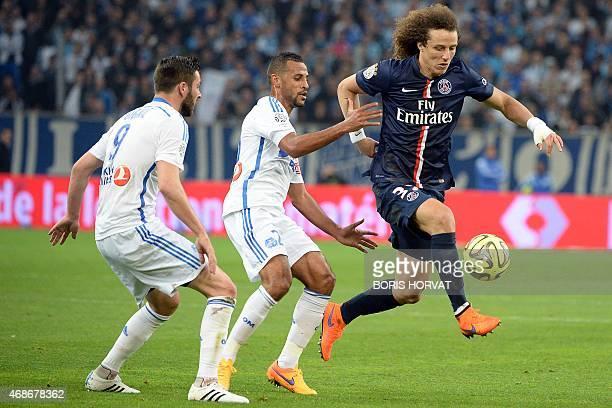 Paris SaintGermain's Brazilian defender David Luiz vies with Marseille's Togolese midfielder JacquesAlaixys Romao and Marseille's French forward...