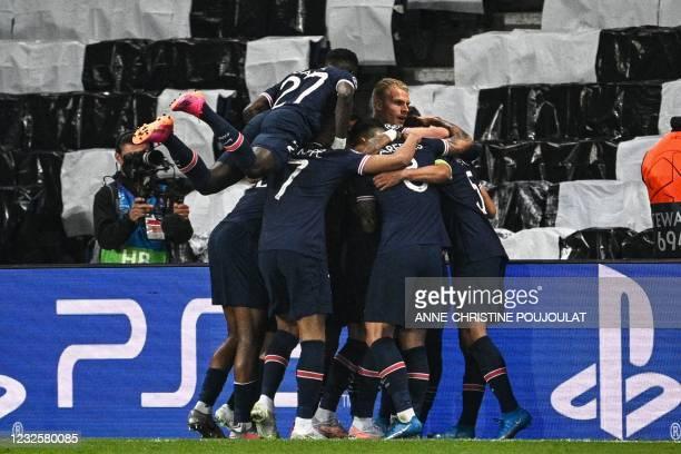 Paris Saint-Germain's Brazilian defender Marquinhos celebrates with his teammates after scoring a goal during the UEFA Champions League first leg...