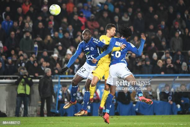 Paris SaintGermain's Brazilian defender Marquinhos jumps for the ball with Strasbourg's French defender Ernest Seka and Strasbourg's Burkinabe...