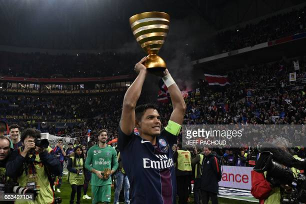 TOPSHOT Paris SaintGermain's Brazilian defender Thiago Silva celebrate with the trophy after winning the French League Cup final football match...