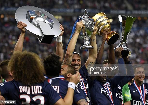 Paris SaintGermain's Brazilian defender Thiago Silva holding up the Ligue 1 trophy Swedish forward Zlatan Ibrahimovic holding up the French Cup...
