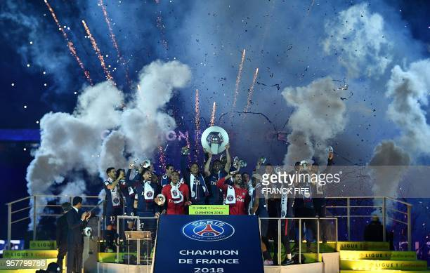 TOPSHOT Paris SaintGermain's Brazilian defender Thiago Silva holds is trophy on the podium after winning the French L1 title at the end of the French...