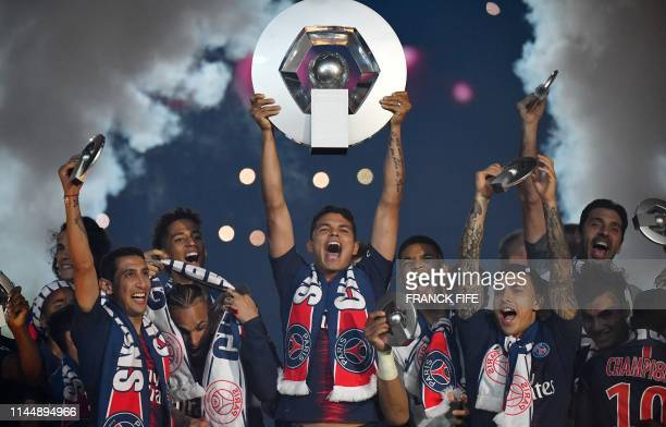 Paris Saint-Germain's Brazilian defender Thiago Silva holds the French L1 winner trophy as he celebrates with team mates at the end of the French...