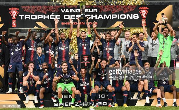 TOPSHOT Paris SaintGermain's Brazilian defender Thiago Silva holds the trophy as he celebrates with teammates after winning the French Trophy of...