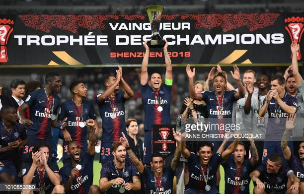 Paris SaintGermain's Brazilian defender Thiago Silva holds the trophy as he celebrates with teammates after winning the French Trophy of Champions...