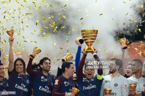 TOPSHOT Paris SaintGermain's Brazilian defender Thiago Silva holds the trophy as he celebrates with teammates German goalkeeper Kevin Trapp French...