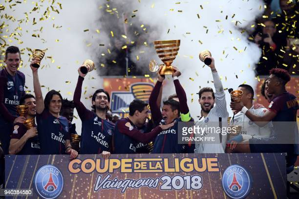 TOPSHOT Paris SaintGermain's Brazilian defender Thiago Silva holds the trophy as he celebrates with teammates after victory in the French League Cup...