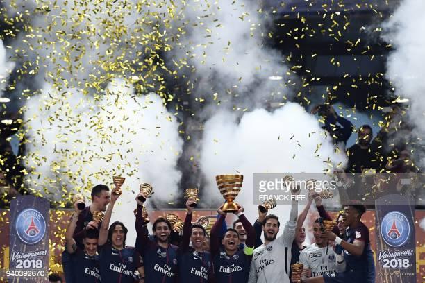 Paris SaintGermain's Brazilian defender Thiago Silva holds the trophy as he celebrates with teammates German goalkeeper Kevin Trapp French goalkeeper...