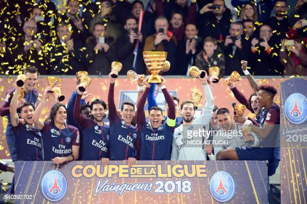 TOPSHOT Paris SaintGermain's Brazilian defender Thiago Silva holds the trophy as he celebrates with teammates German goalkeeper Kevin Trapp French...