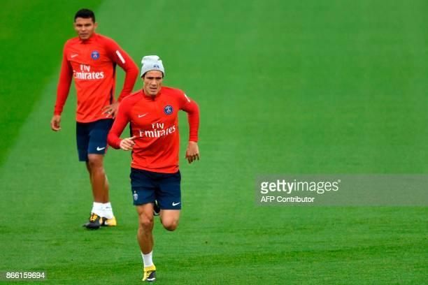 Paris SaintGermain's Brazilian defender Thiago Silva looks at Paris SaintGermain's Uruguayan forward Edinson Cavani as he run while they both take...