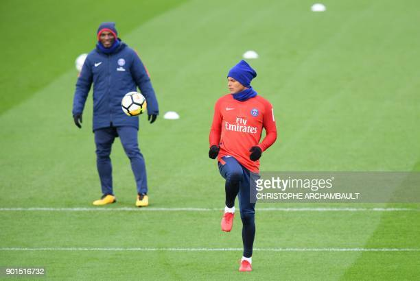 Paris SaintGermain's Brazilian defender Thiago Silva plays the ball next to assistant coach Zoumana Camara during a training session of French L1...