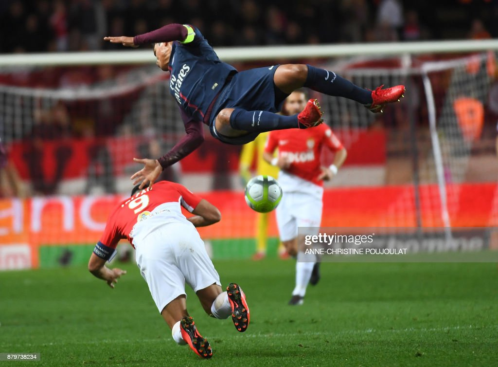 TOPSHOT - Paris Saint-Germain's Brazilian defender Thiago Silva (up) vies for the ball with Monaco's Colombian forward Radamel Falcao (L) during the French L1 football match between Monaco and Paris Saint-Germain (PSG) at the Louis II stadium, in Monaco, on November 26, 2017. /