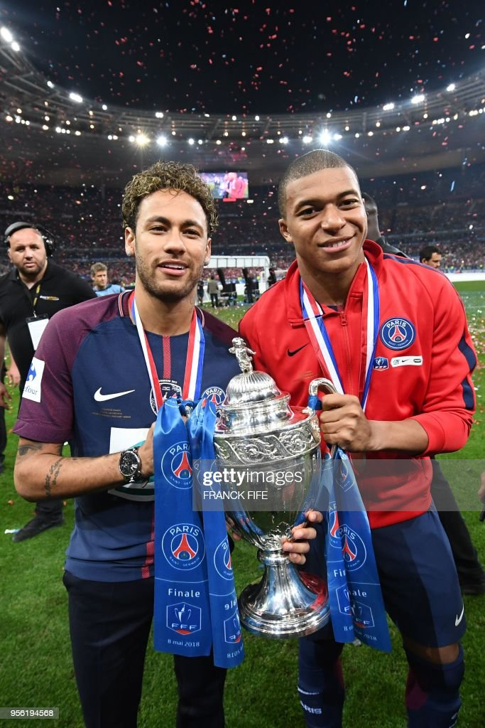 TOPSHOT - Paris Saint-Germain's Brazilian forwar Neymar Jr (L) and Paris Saint-Germain's French forward Kylian Mbappé celebrate with the trophy at the end of the French Cup final football match between Les Herbiers and Paris Saint-Germain (PSG), on May 8, 2018 at the Stade de France in Saint-Denis, outside Paris.