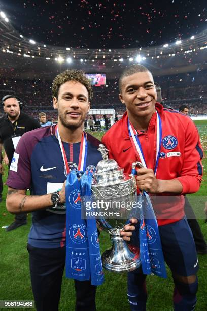 TOPSHOT Paris SaintGermain's Brazilian forwar Neymar Jr and Paris SaintGermain's French forward Kylian Mbappé celebrate with the trophy at the end of...