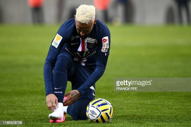 Paris Saint-Germain's Brazilian forward Neymar adjusts his sock during the French League Cup semi-final football match between Stade de Reims and...