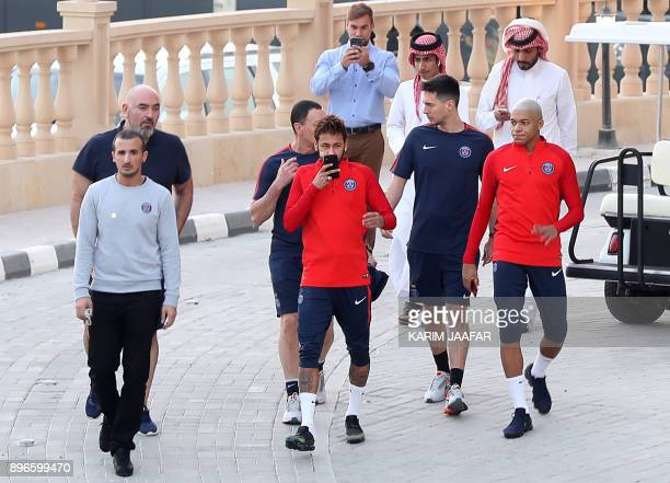 Paris SaintGermain's Brazilian forward Neymar and French forward Kylian Mbappe walk among team members and locals in Doha on December 21 during a...