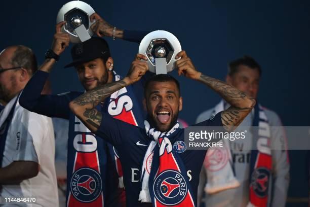 Paris SaintGermain's Brazilian forward Neymar and Paris SaintGermain's Brazilian defender Dani Alves celebrate with their Champion's trophy at the...