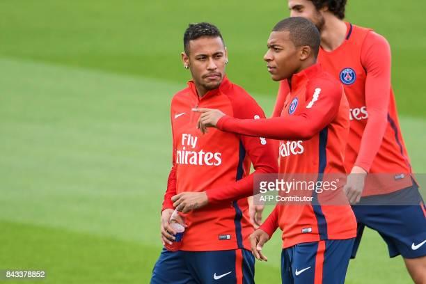 Paris SaintGermain's Brazilian forward Neymar and Paris SaintGermain's French forward Kylian Mbappe talk during a training session at the club's...